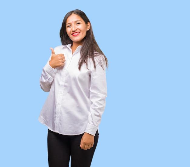 陽気で興奮して、笑みを浮かべて、彼女の親指を上げる、成功と承認、okのジェスチャーの概念の若いインド人女性の肖像画