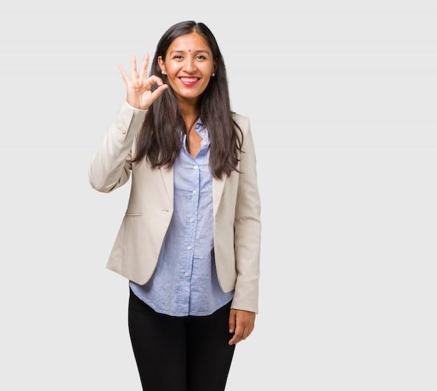 陽気で自信を持ってokジェスチャー、興奮して叫んで、承認と成功の概念を行う若いビジネスインド人女性