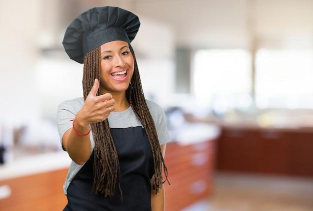 陽気で興奮して、笑みを浮かべて、彼女の親指を立てる、成功と承認、okのジェスチャーの概念の若い黒ベイカー女性の肖像画