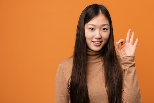若いかなり中国人女性が明るく自信を持ってokのジェスチャーを示します。