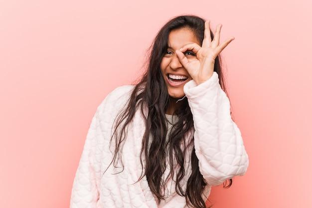 パジャマを着ている若いインド人女性は、目で[ok]ジェスチャーを維持する興奮しました。