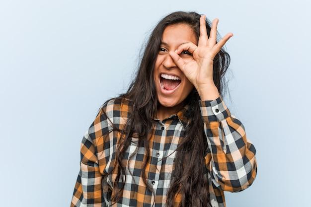 若いクールなインドの女性は、目にokのジェスチャーを維持することに興奮しています。