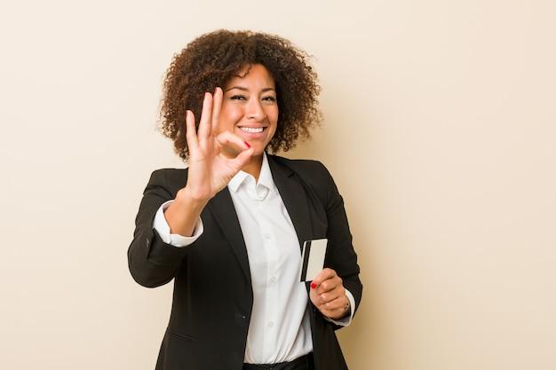 陽気な自信を持ってokジェスチャーを示すクレジットカードを保持している若いアフリカ系アメリカ人女性。