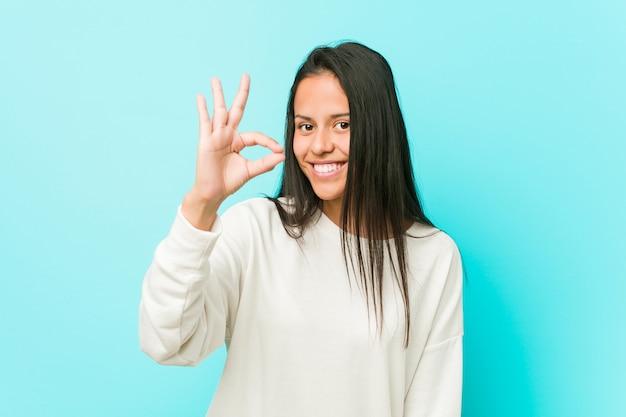 若いかなりヒスパニック系女性の陽気な自信を持ってokのジェスチャーを示します。