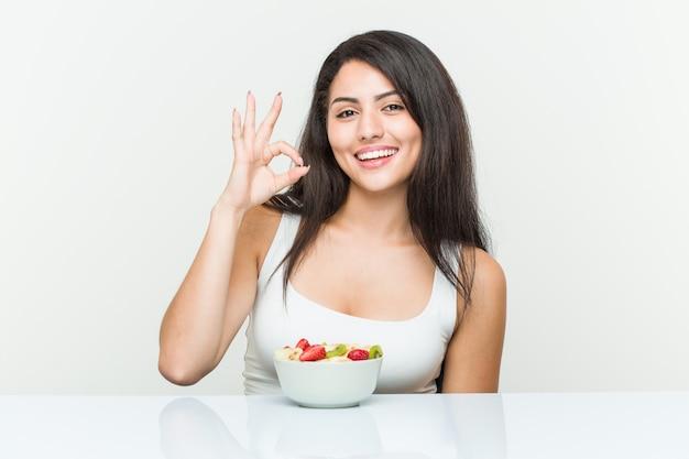 フルーツボウルを食べる若いヒスパニック系女性が明るく、自信を持って[ok]ジェスチャーを示します。