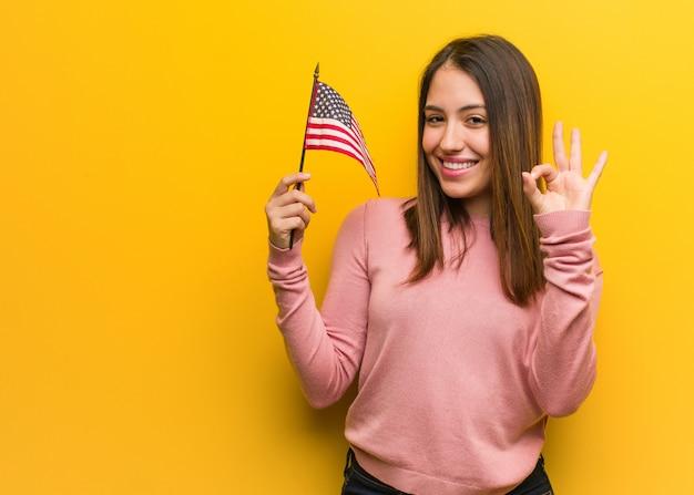 アメリカ合衆国の旗を保持している若いかわいい女性が明るく、自信を持ってokのジェスチャーを行う