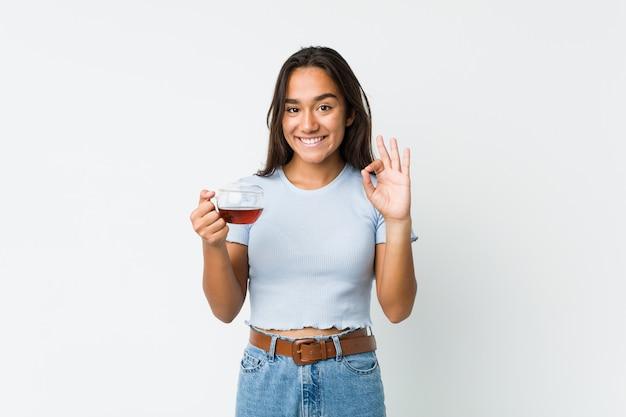 お茶のカップを保持している若いインドの陽気な自信を持ってokジェスチャーを示す