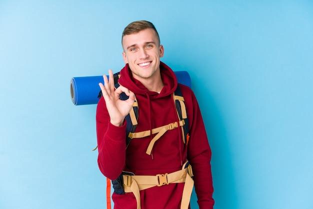 若い旅行者の白人男性は明るく、自信を持ってokのジェスチャーを示します。