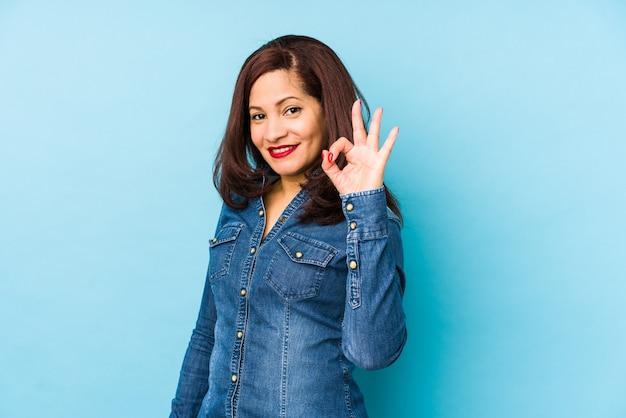 陽気な自信を持ってokジェスチャーを示す青い壁に分離された中年ラテン女性。