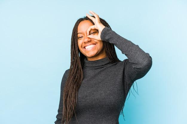 青い壁に分離された若いアフリカ系アメリカ人女性は、目で[ok]ジェスチャーを維持する興奮しています。