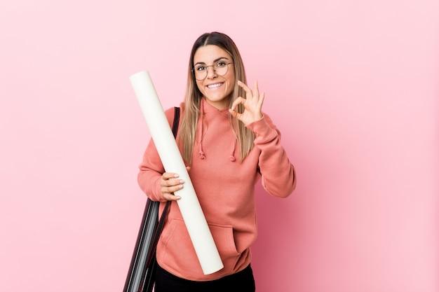 [ok]ジェスチャーを示す陽気な自信を持って建築を勉強している若い女性。