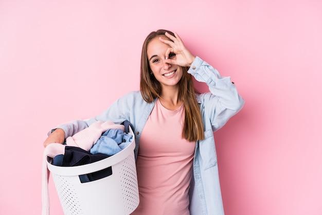 汚れた服を拾う若い女性は、目で[ok]ジェスチャーを維持して興奮しています。