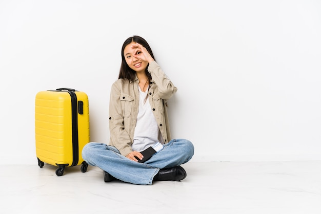 搭乗券を持って座っている若い旅行者の女性は、目にokのジェスチャーを維持して興奮しています。