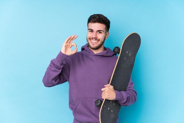 若い白人のスケーターの男は、明るく自信を持ってokのジェスチャーを示します。