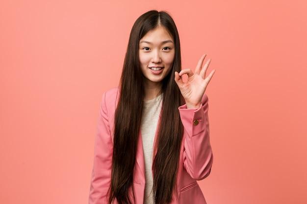 陽気な自信を持ってokジェスチャーを示すピンクのスーツを着ている若いビジネス中国の女性。