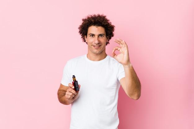 若い白人の巻き毛の男は、元気で自信を持ってokジェスチャーを示しています。