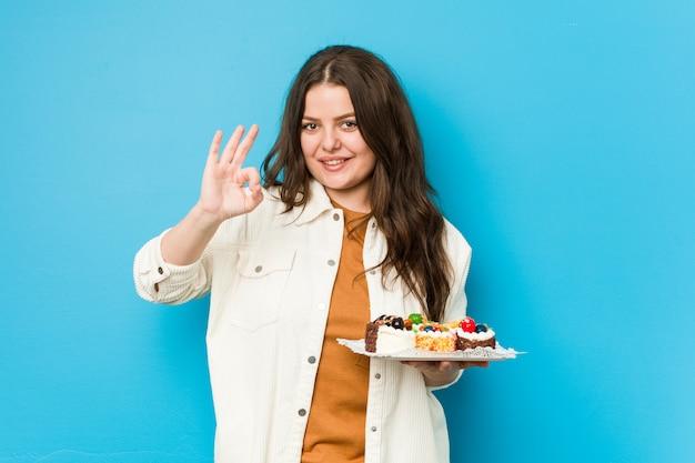 甘いケーキを保持している若い曲線の女性は明るく、自信を持ってokのジェスチャーを示します。