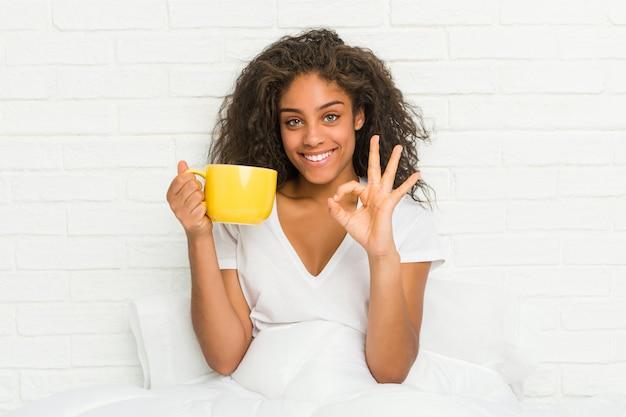 陽気な自信を持って[ok]ジェスチャーを示すコーヒーマグカップを保持しているベッドに座っている若いアフリカ系アメリカ人女性。