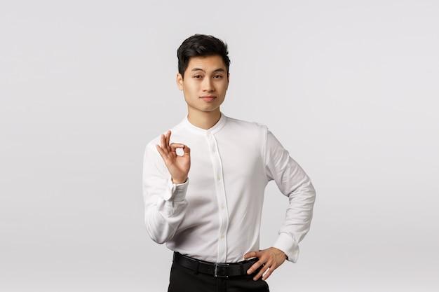 良い仕事、良い仕事。大丈夫、良いokジェスチャーを示すフォーマルな衣装でハンサムな断定的な若い成功したアジア系のビジネスマン
