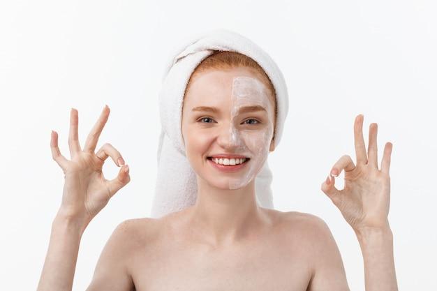 美容トリートメント。女性の顔に保湿クリームスキンケア製品を適用してokサインを作る