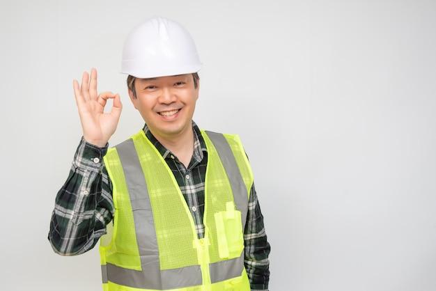 中年のアジア人労働者が手を挙げてokとサインします。