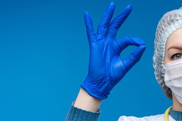 Доктор в форме защиты, показывая ok знак рукой.
