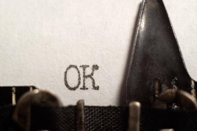 レトロなタイプライターを使用して、白い紙に「ok」と入力した単語