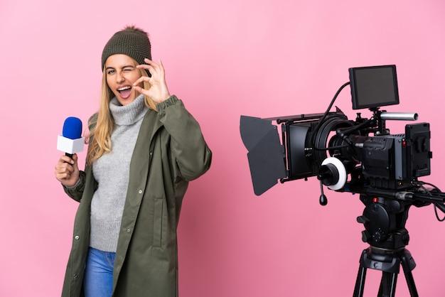 マイクを押しながら指でokの標識を示す孤立したピンクのニュースを報告するレポーター女性