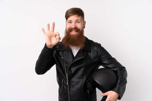 指でokの標識を示す孤立した白でオートバイのヘルメットを保持している長いひげを持つ赤毛の男