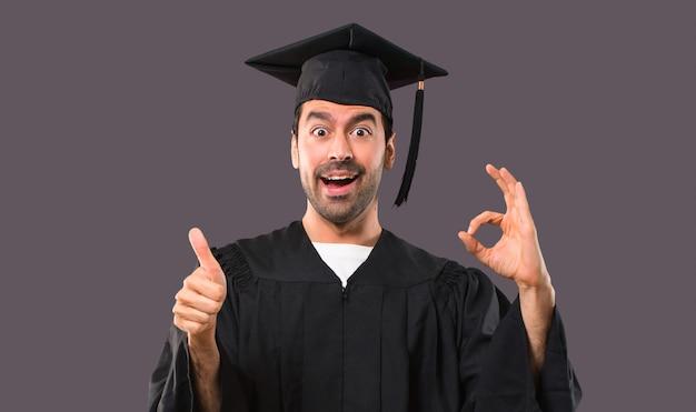彼の卒業式の日の男大学で指でok記号を表示し、親指をあげて