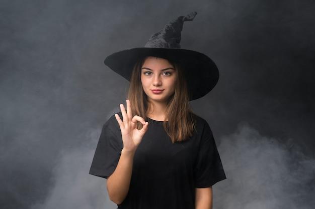 指でokサインを示す孤立した暗い壁の上のハロウィーンパーティーの魔女の衣装を持つ少女