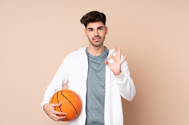 孤立した背景に若い男がバスケットボールをし、okサインを作る