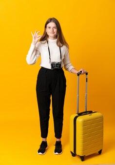 指でokサインを示すスーツケースと旅行者のティーンエイジャーの女の子の全身