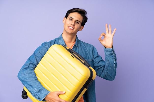 旅行スーツケースとokサインを作る休暇で紫色の壁の上の男