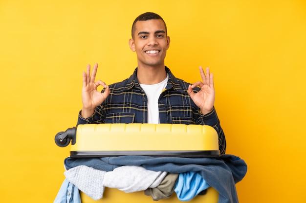 指でokの標識を示す分離の黄色の壁の上の服の完全なスーツケースを持つ旅行者男