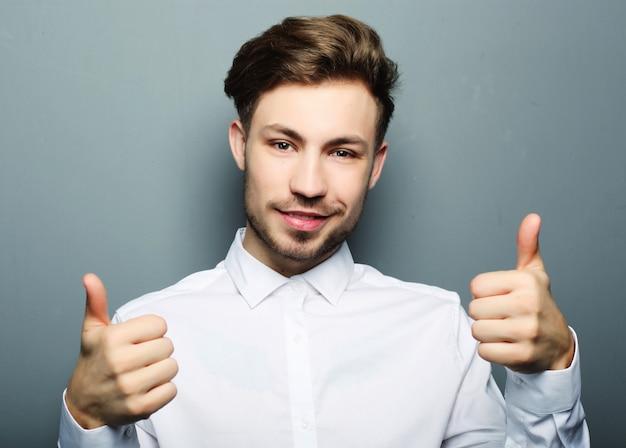 ハンサムな男の幸せな笑顔、[ok]ジェスチャー記号で手を握る
