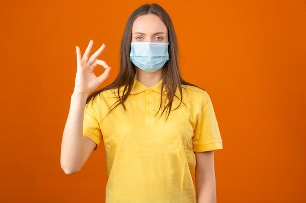 黄色のポロシャツとオレンジ色の背景に立っているokサインを示す医療用防護マスクの若い病気の女性