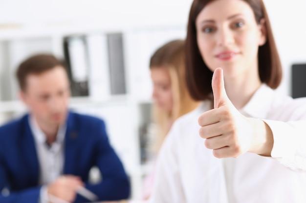 女性の腕は、創造的な人々のオフィスのクローズアップで親指でokまたは承認を表示します。高レベルの製品の深刻なオファー会議調停ソリューションアドバイザー参加コンセプト