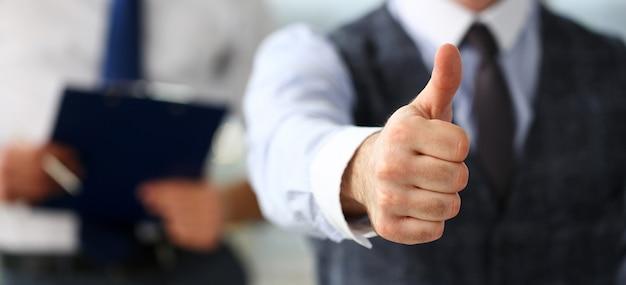 男性の腕は、オフィスでの会議中にokまたは確認を表示します