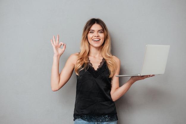 ラップトップコンピューターを押しながらokのしぐさを示す幸せな笑顔の女性
