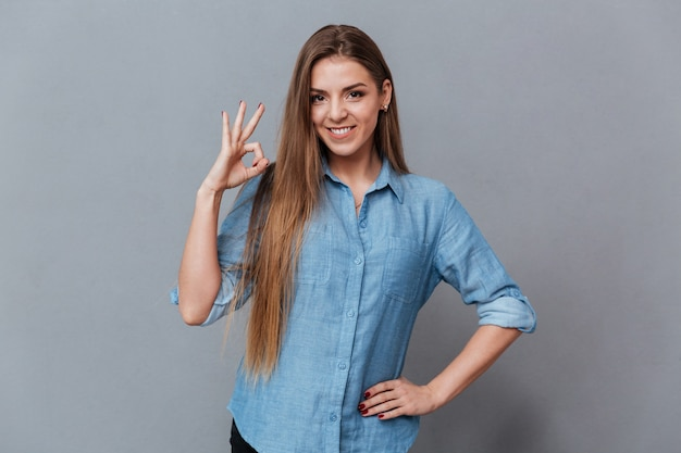 Okの標識を示すシャツで笑顔の女性