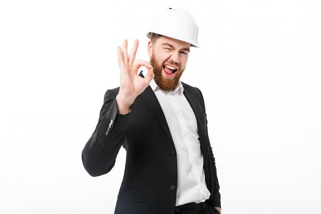Okの標識を示す保護用のヘルメットで幸せなひげを生やしたビジネス男
