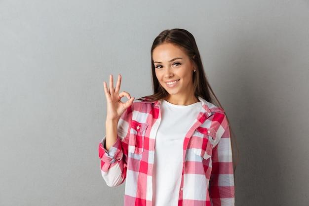 [ok]ジェスチャーを示す市松模様のシャツで笑顔の若いブルネットの女性の写真をクローズアップ