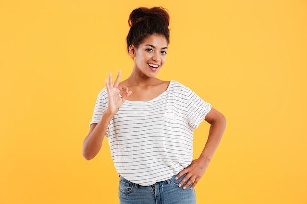 [ok]のジェスチャーを示すと黄色で分離された笑顔の白いプルオーバーで幸せな若いアフリカ女性