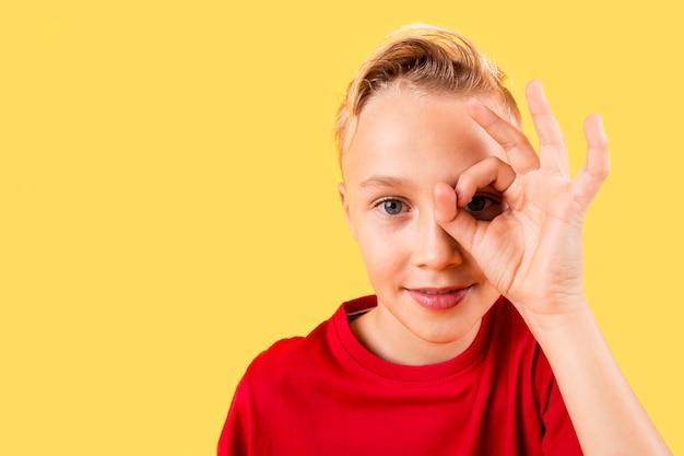 Okの標識で目を覆っている少年