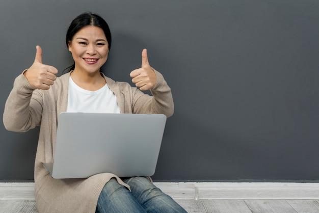 Okサインを示すラップトップを持つ女性