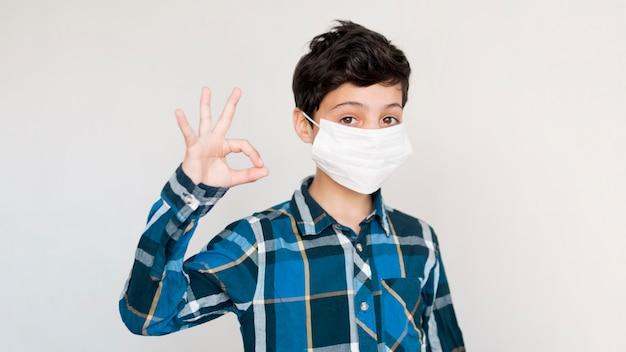 Okの標識を示すマスクを持つ少年