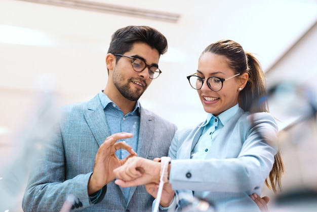 新しい腕時計を買うスーツを着た多文化のカップル。時計とokの標識を示す男を着ている女性。テックストアのインテリア。