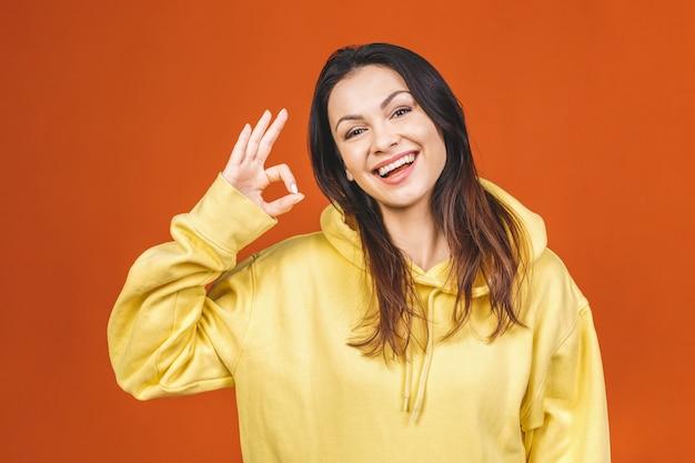 オレンジ色の背景に対して分離されたokの標識を示す若い幸せな陽気な女性。
