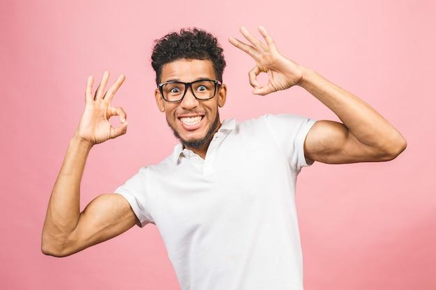 手と指でokの標識を行う肯定的な笑みを浮かべて分離ピンクの背景の上に立っている白いシャツを着てアフロの髪の若いアメリカ人。成功した表現。